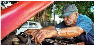 Elderly man mechanic working on his vehicle