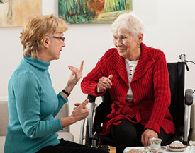 Caregiver connecting with her client over tea and cake
